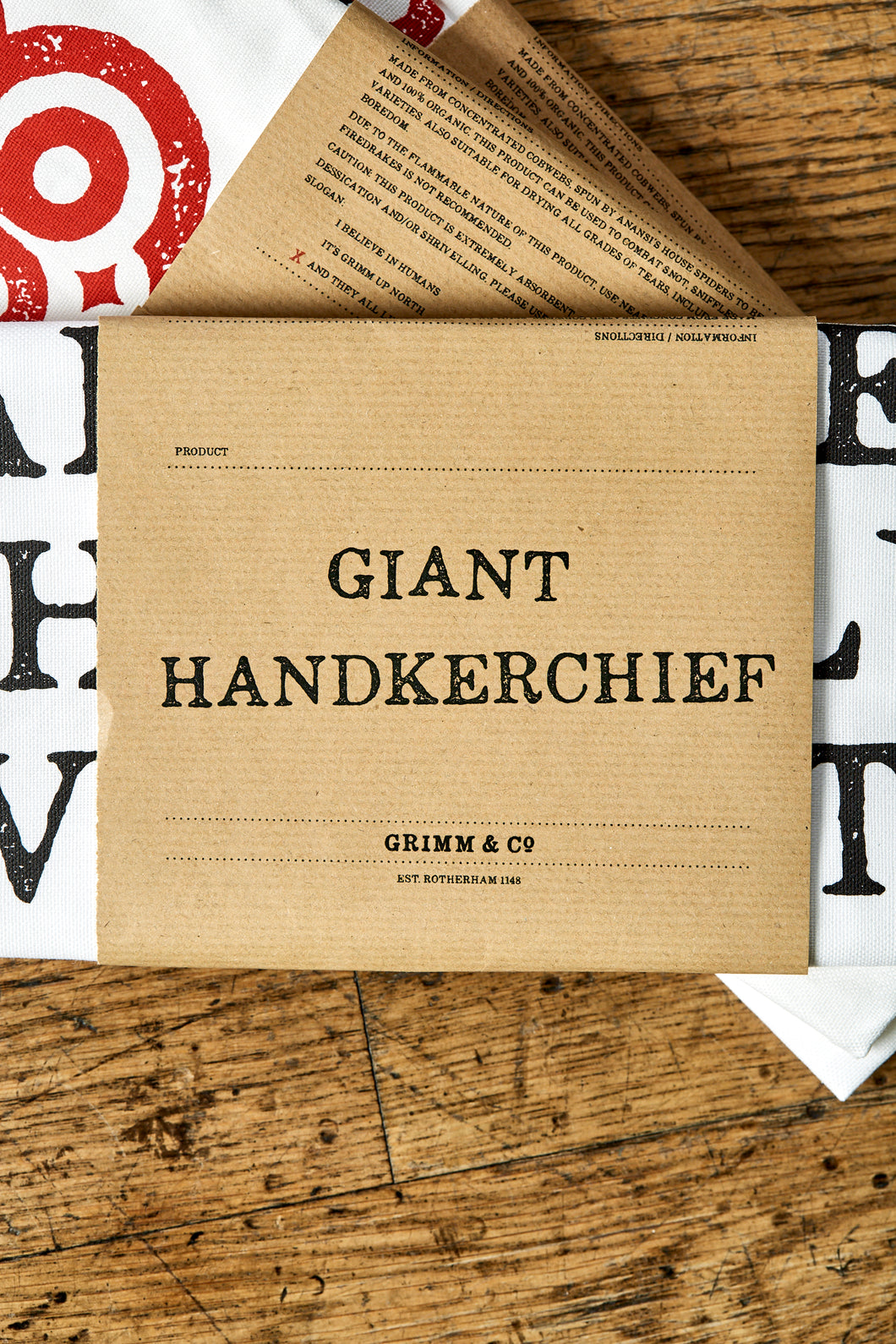 Image shows the kraft paper label of the Giant Handkerchief, otherwise known as a cotton tea towel.