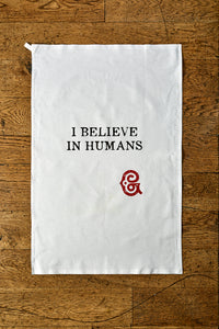 Image shows the Giant Handkerchief unfolded to display slogan printed in black on white cotton tea towel. Slogan reads 'I BELIEVE IN HUMANS' with the Grimm & Co red 'G' monogram underneath.