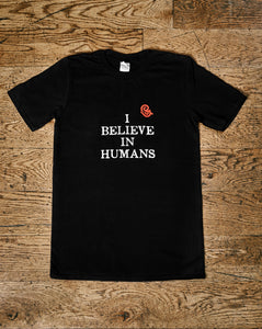Image shows the Human Disguise t-shirt made from black cotton and printed with the slogan 'I BELIEVE IN HUMANS' in white ink and the Grimm & Co red 'G' monogram at the top right of the slogan.
