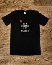 Load image into Gallery viewer, Image shows the Human Disguise t-shirt made from black cotton and printed with the slogan 'IT'S GRIMM UP NORTH' in white ink and the Grimm & Co red 'G' monogram at the top left of the slogan.
