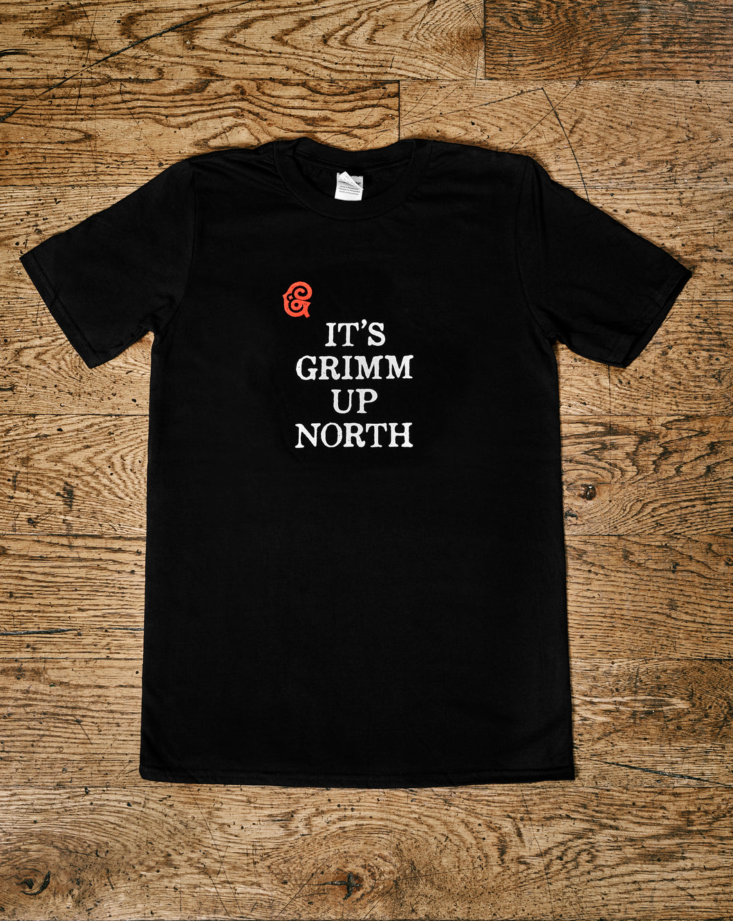 Image shows the Human Disguise t-shirt made from black cotton and printed with the slogan 'IT'S GRIMM UP NORTH' in white ink and the Grimm & Co red 'G' monogram at the top left of the slogan.