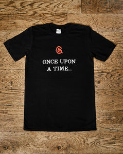 Image shows the Human Disguise t-shirt made from black cotton and printed with the slogan 'ONCE UPON A TIME' in white ink and the Grimm & Co red 'G' monogram at the top centre of the slogan.