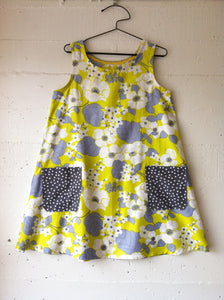 sleeveless dress in printed fabric on a hanger