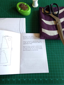open instruction booklet and folded sewing pattern. Arrangement of folded fabric, large scissors, pin cushion and a spool of thread