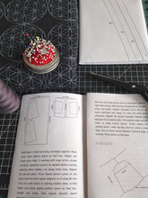 open instruction booklet with scissors, folded sewing pattern and fabric, pin cushion and spool of thread