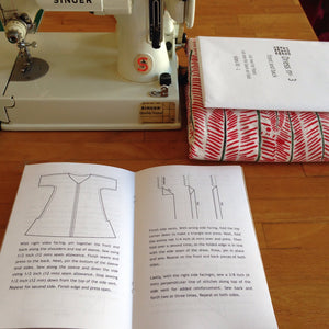 open instruction booklet, fabric, sewing pattern and sewing machine