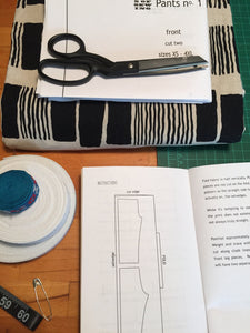 Open instruction book with scissors on top of a folded sewing pattern and fabric. Rolled elastic, fabric trim, safety pin, measuring tape