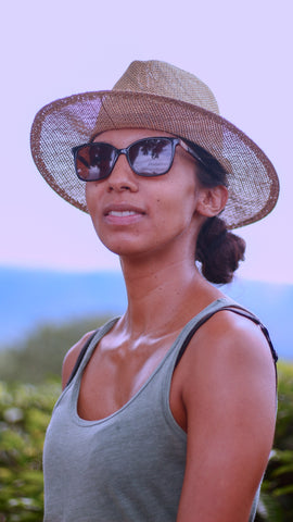 Woman standing in tea plantation with straw hat and sunglasses