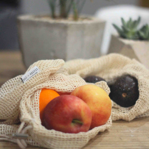 organic cotton reusable produce bag with oranges apples and avocado