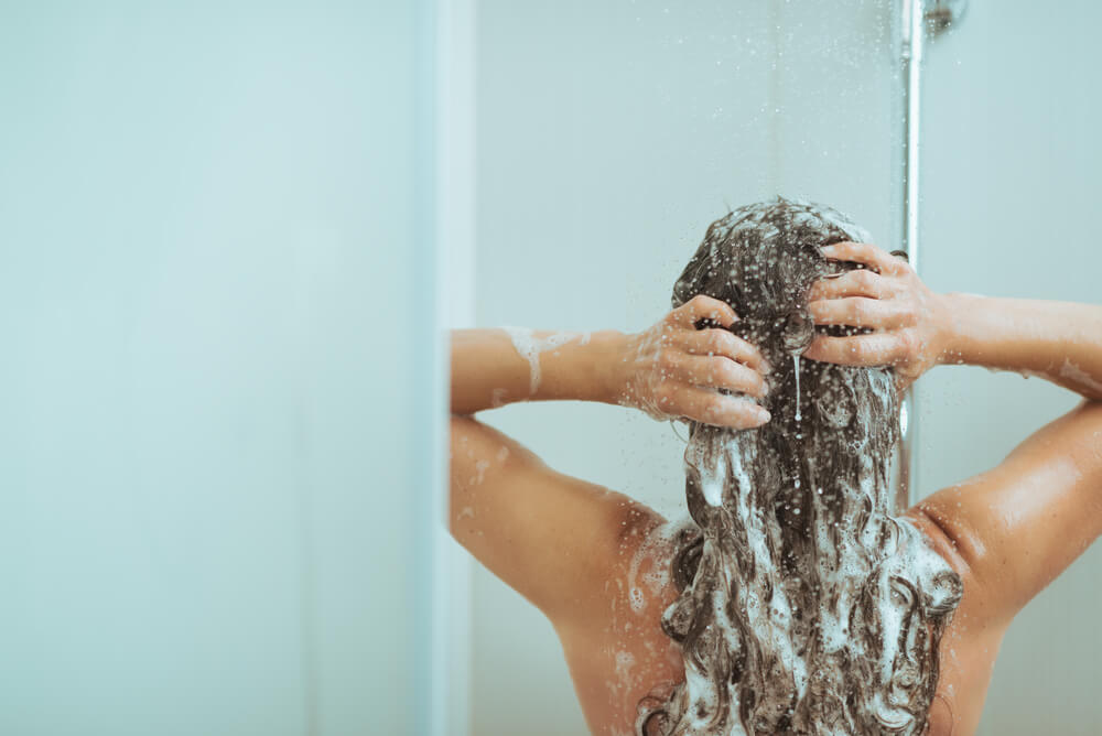 woman taking short shower as water conservation activity