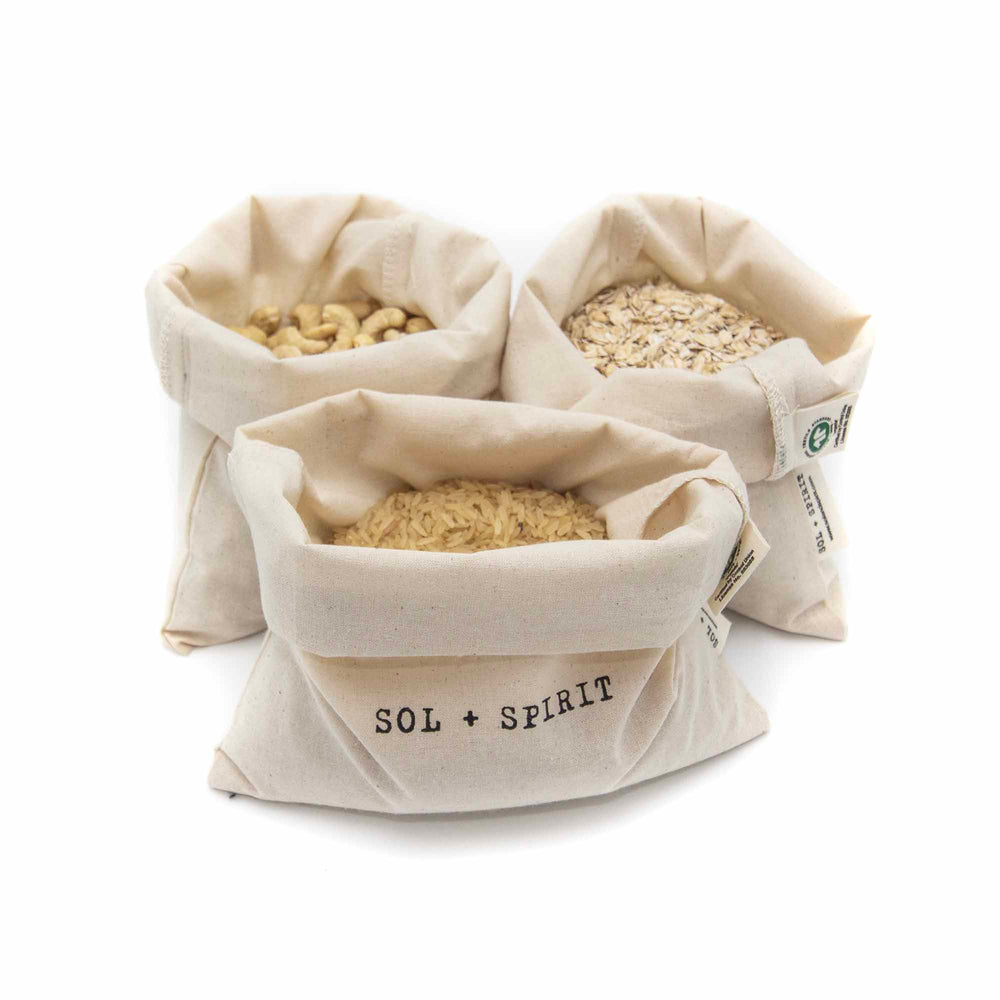 three drawstring organic cotton bags filled with food
