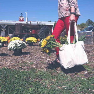 carrying organic cotton tote bag at the farmers market