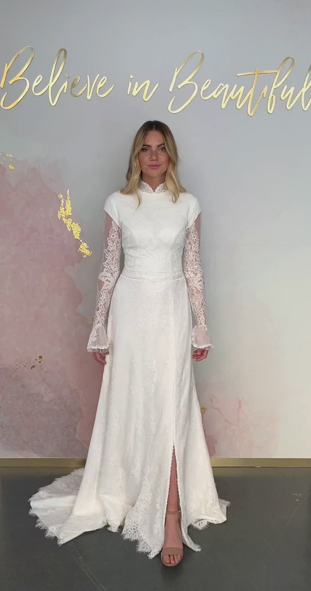A video featuring our Clara wedding dress and its chic mock neck. lace bell sleeves, and slit in the skirt.