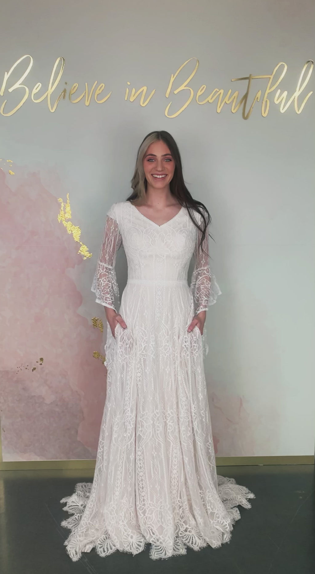 A video featuring our Arwen wedding dress with its full lace A-line skirt, whimsical bell sleeves, and eyelash lace detailing at the hem.