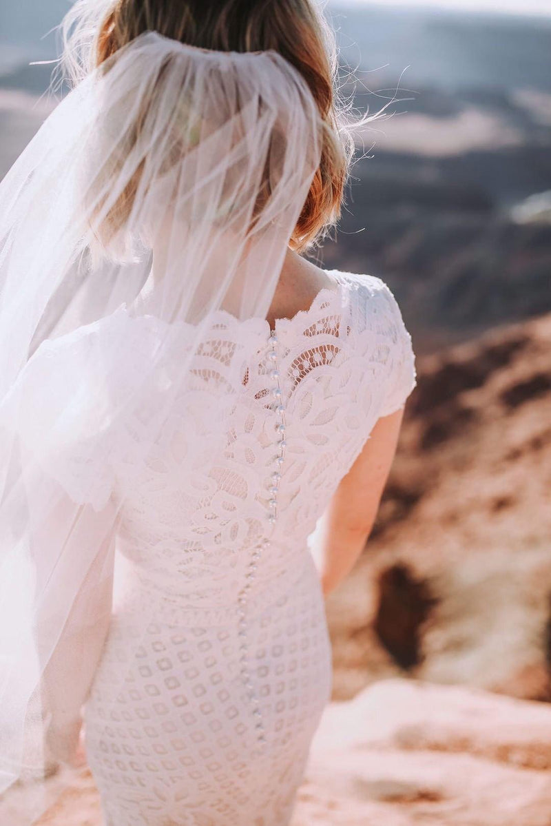 Real bride wearing a modest wedding dress with Boat neckline with delicate scalloped sleeves, style Luciana, is part of the Wedding Collection of LatterDayBride, a Salt Lake City bridal shop.