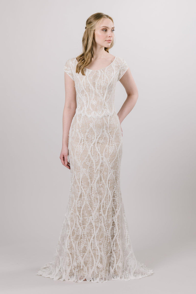 Chantilly embroidered lace cascades vertically down the entire sheath silhouette of this modest wedding dress, elongating the figure flawlessly.