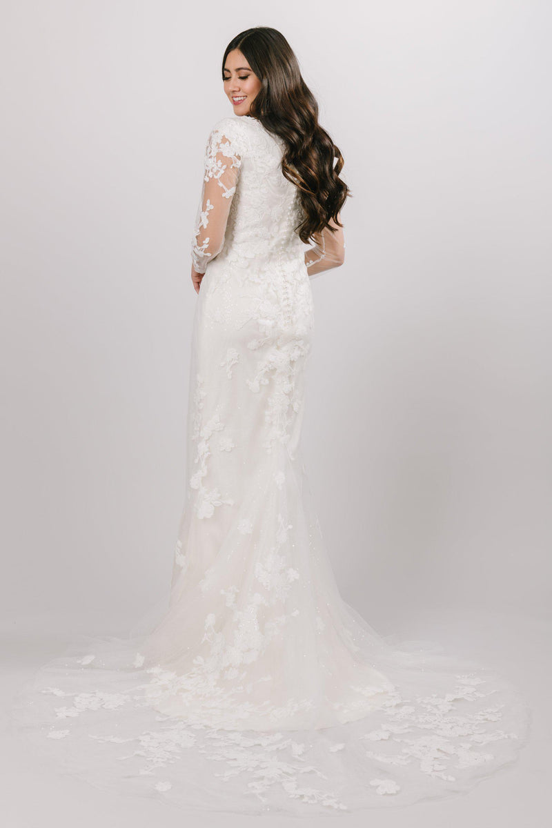 This fit-and-flare, modest wedding dress is created with perfecting satin underneath, sequined tulle and Alencon lace on top adding detail and a slight shimmer.