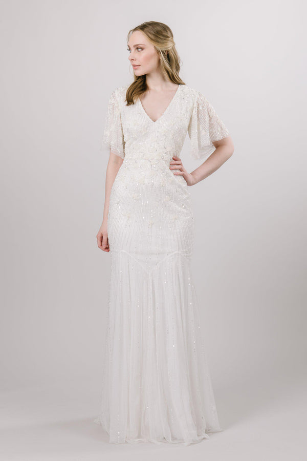 This fully jeweled modest wedding gown features a delicate flutter sleeve, and soft mermaid silhouette. Available in ivory.