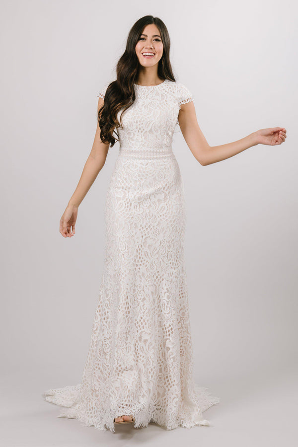 Modest laced wedding dress with capped sleeves featuring a soft aline look from bridal shop in Salt Lake City Utah