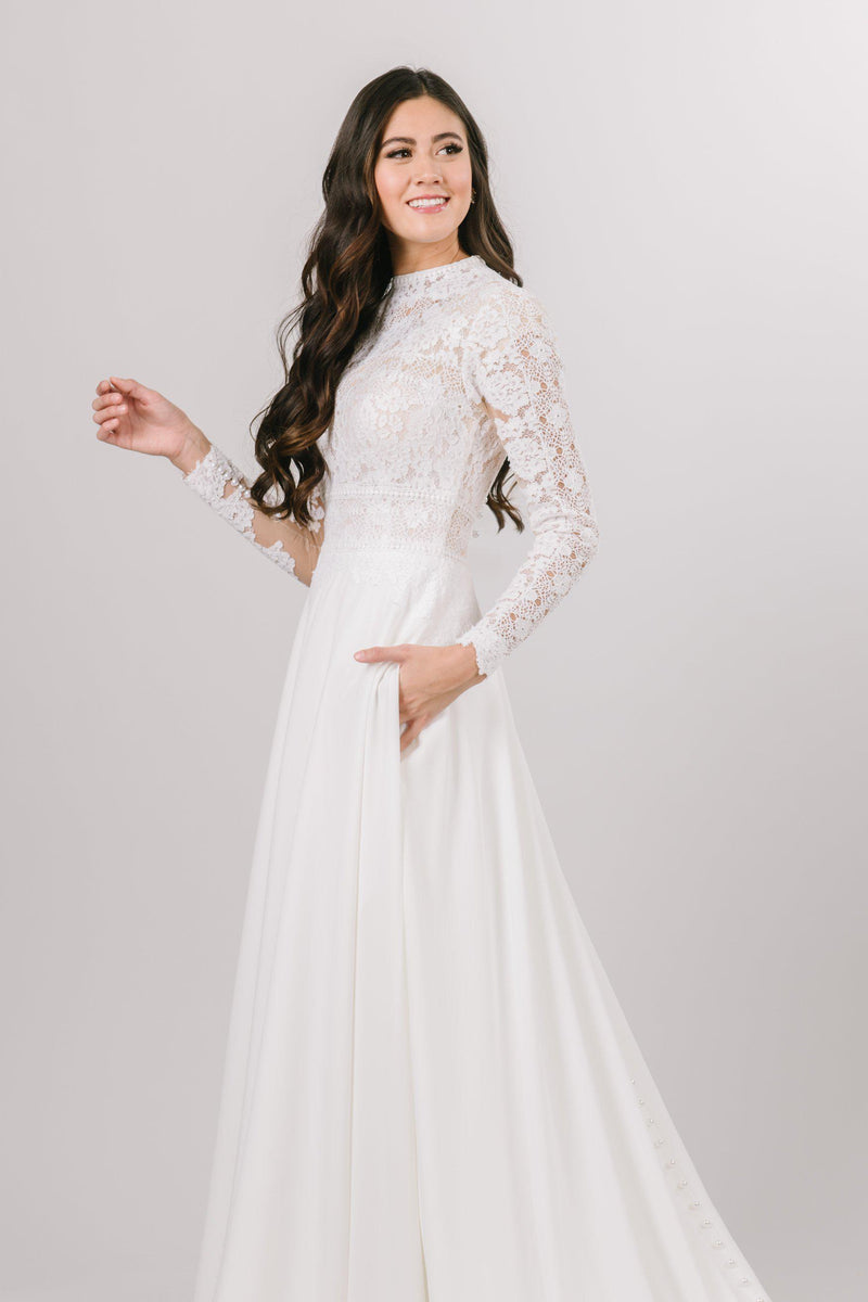 This wedding dress features a lace top with a high neckline, chiffon skirt, and long sleeves. Back lined with buttons all the way down to the train.
