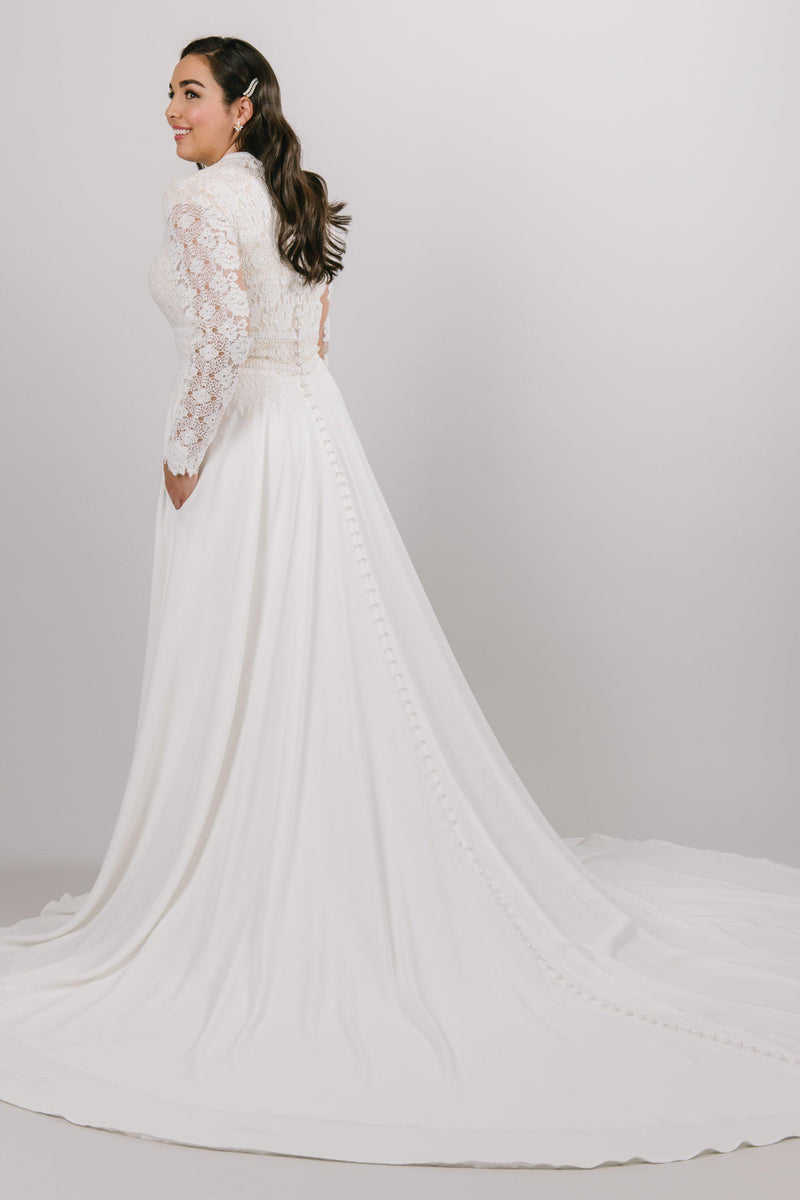 This wedding dress features a lace top with a high neckline, chiffon skirt, and long sleeves.