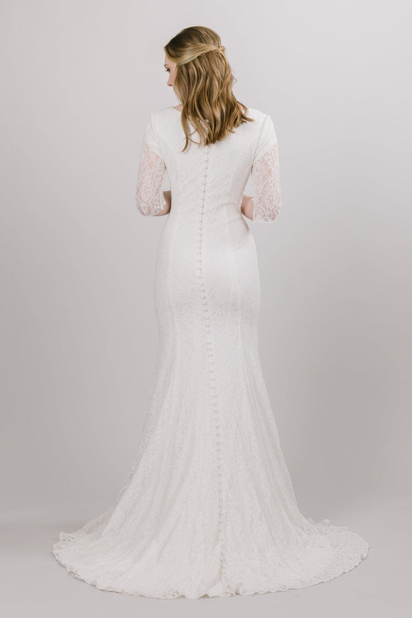 This affordable modest wedding dress features a lovely, modern lace pattern and beautiful princess seams! Available in ivory.