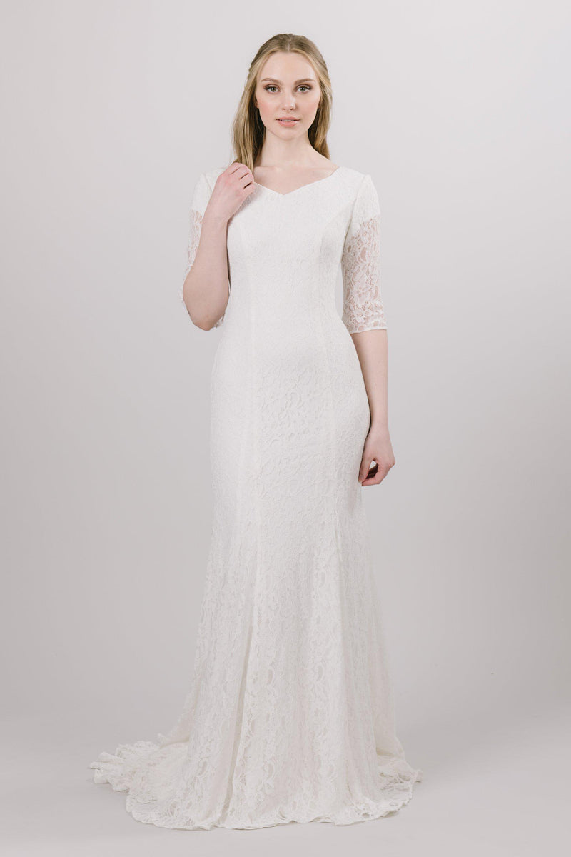 This modest wedding dress features a lovely, modern lace pattern and beautiful princess seams! Available in ivory.