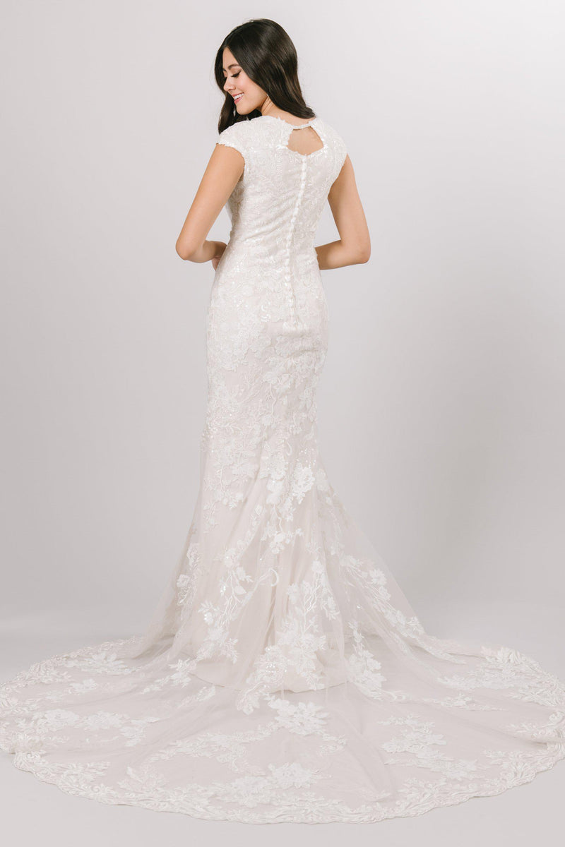 Modest fit and flare wedding dress with a high neck and cap sleeves from bridal shop in Salt Lake City Utah