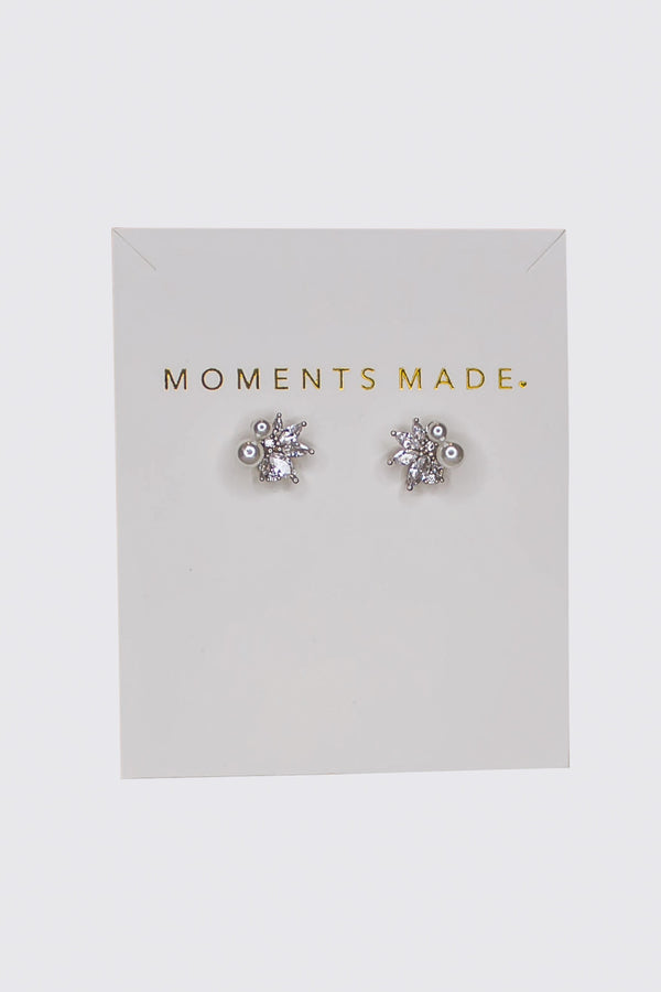 The earring is a floral design composed of marquise-cut crystals, is paired with two pearls.