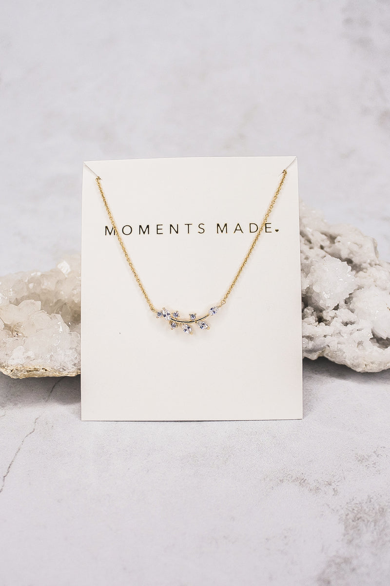 The necklace features an alluring array of leaf marquise-cut crystals. This necklace is charming and great for layering!  Placed in front of a geode.