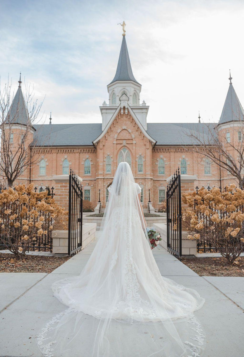 Back view of a modest wedding ballgown with cathedral length veil and lace detail. From LatterDayBride, a modest wedding dress shop in Salt Lake City, Utah