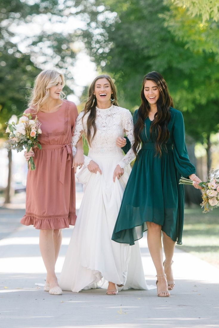This image depicts a bride with two of her bridesmaids in a pink and green dress.