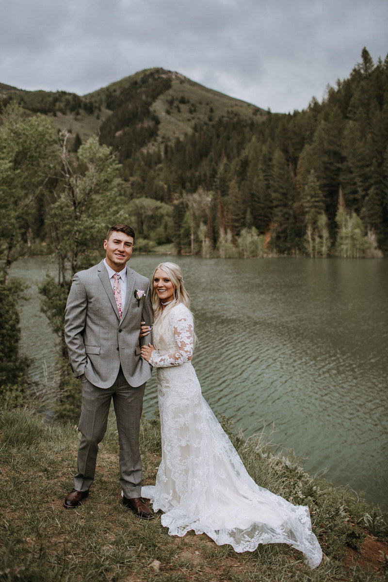 Real Bride wearing a modest wedding dress, visually stunning floral lace softly makes its way from long sleeves all the way down to the train. Tulle and Luxe silky charmeuse lining, modest wedding gown salt lake city, front view