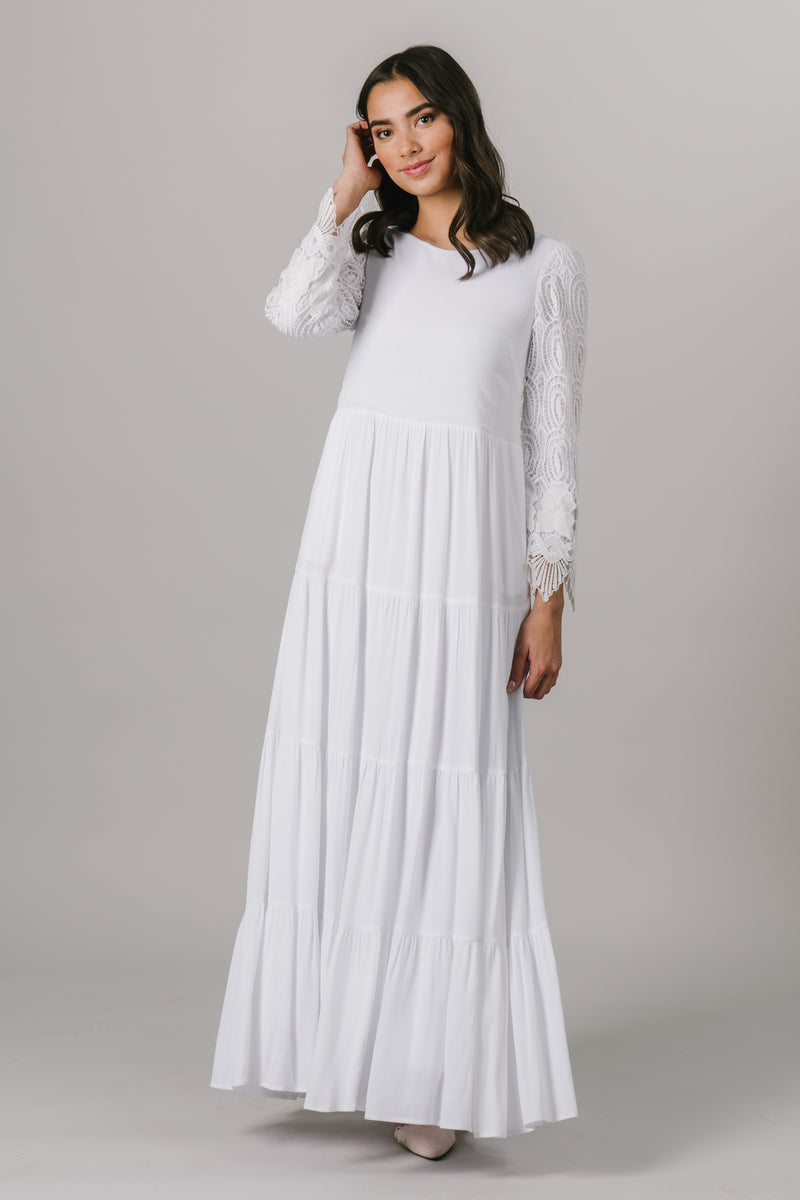 This LDS temple dress features fully lined lace sleeves and a multiples tiers through the skirt. It includes two pockets.