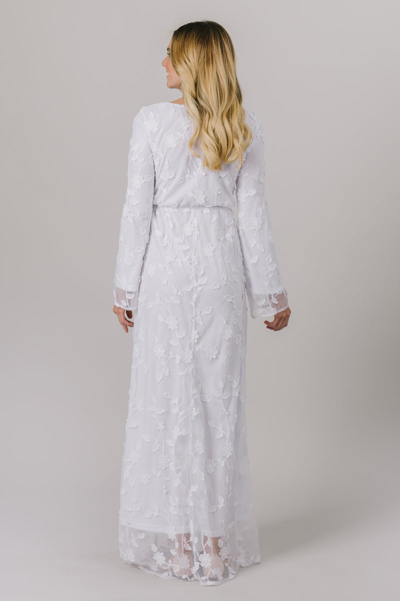 This LDS temple dress features a fully lined, floral lace with a cinched waistband and flowy long sleeves. It includes two pockets. This temple dress is from LatterDayBride in downtown Salt Lake City.