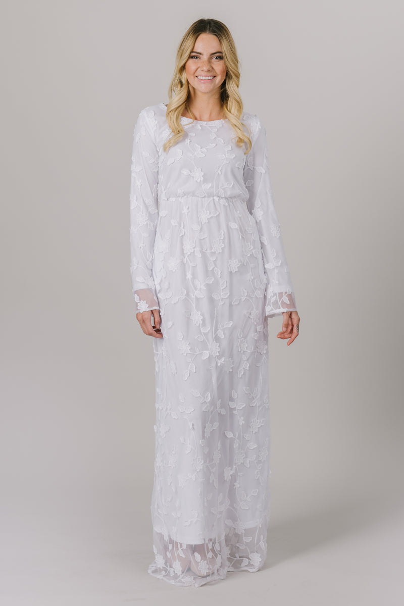 This LDS temple dress features a fully lined, floral lace with a cinched waistband and flowy long sleeves. It includes two pockets.