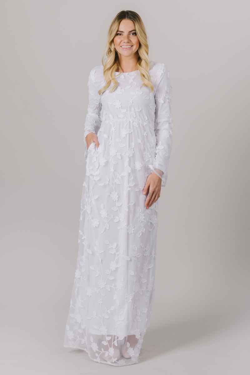 This LDS temple dress features a fully lined, lovely floral lace with a cinched waistband and gorgeous flowy long sleeves. It includes two functional pockets.
