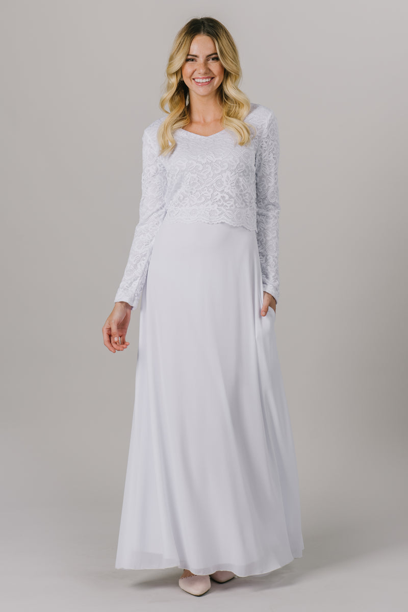 This LDS temple dress features a fully lined, loose lace bodice with a flattering waistband. It includes two pockets and a zipper close.