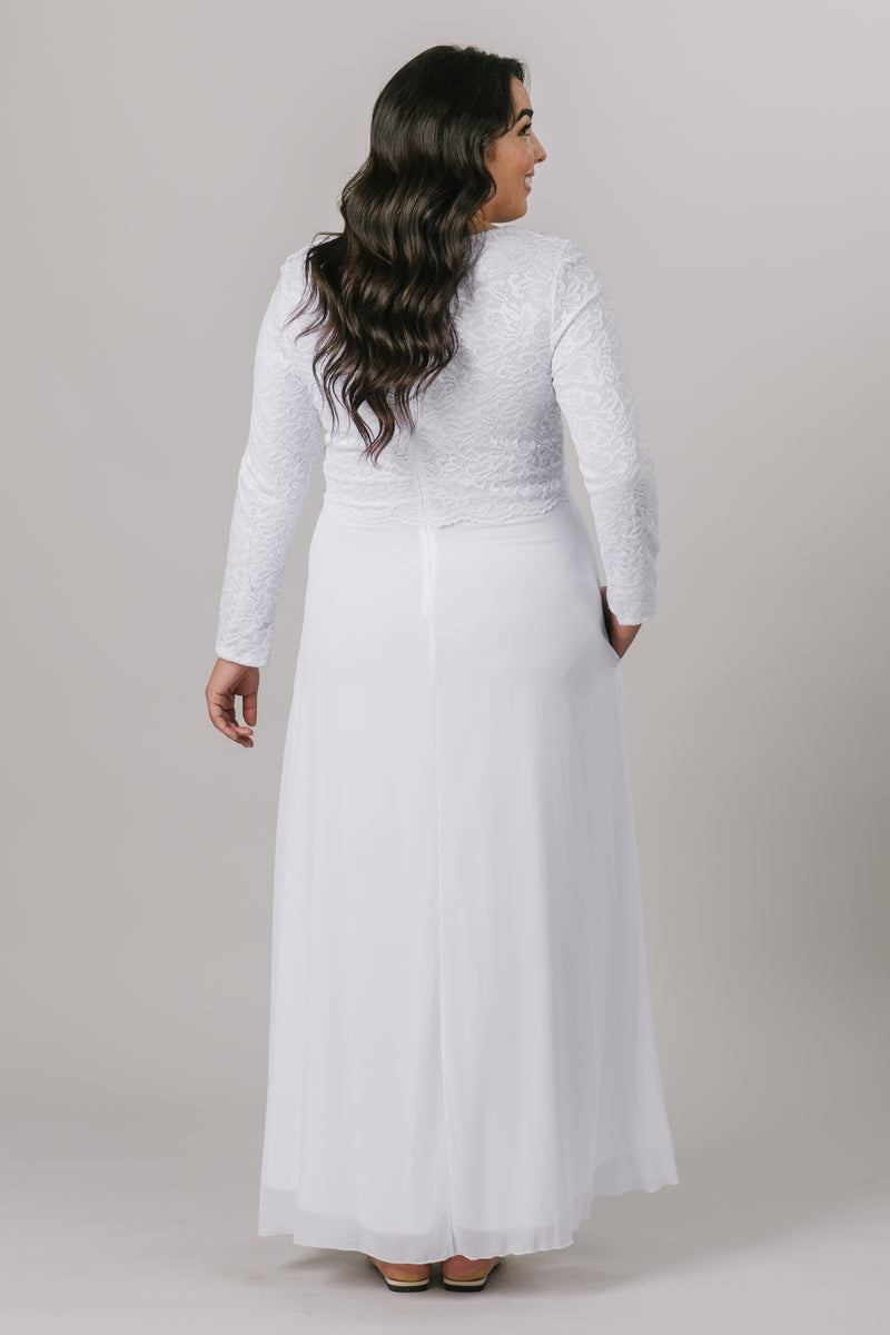 This plus size temple dress features a fully lined, loose lace bodice with a flattering waistband. It includes two pockets and a zipper close. From a bridal shop in downtown Salt Lake City.