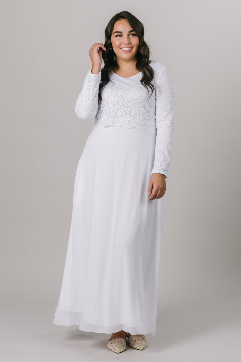 This plus size temple dress features a fully lined, loose lace bodice with a flattering waistband. It includes two pockets and a zipper close.