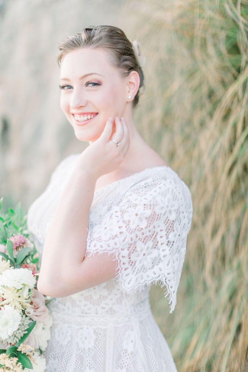 Real bride wearing a boho lace modest wedding dress with flutter sleeves. This modest wedding dress is from LatterDayBride, a bridal shop located in downtown Salt Lake City, Utah.