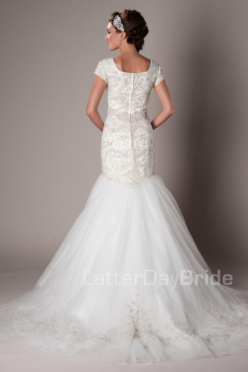 This princess sweetheart neckline and bodice has a sleek satin waistband and a fitted dropped skirt that flows into layers of tulle, part of our modest  utah wedding gown collection back view