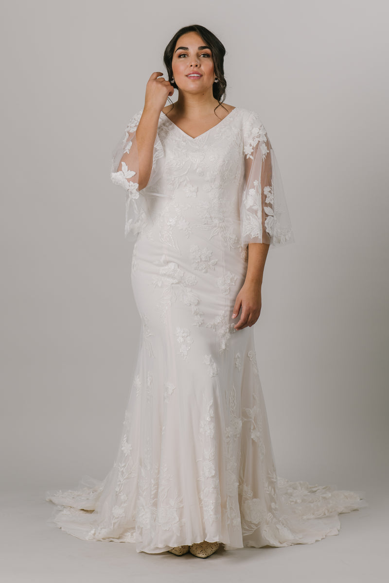 This unique modest wedding gown is like nothing you've seen! It features a v-neckline, fitted silhouette, and gorgeous flowery lace. This gown provides such an amazing fit with details you'll love! Available in Ivory and Ivory/DecoGold.  Style Love: This gown has the most unique flutter sleeves! They're unlike anything else we have in the shop!