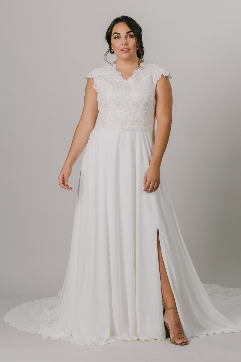 This plus-size wedding dress is an A-line fit featuring a beautiful beaded bodice. Complete with a flattering v-neckline and bead belt, this gown also features a fun slit in the front.