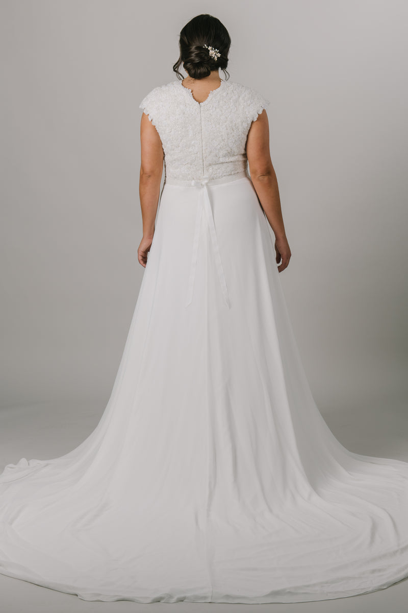 This plus-size wedding dress is an A-line fit featuring a beautiful beaded bodice. Complete with a flattering v-neckline and bead belt, this gown also features a fun slit in the front. From a bridal shop called LatterDayBride in downtown Salt Lake City.