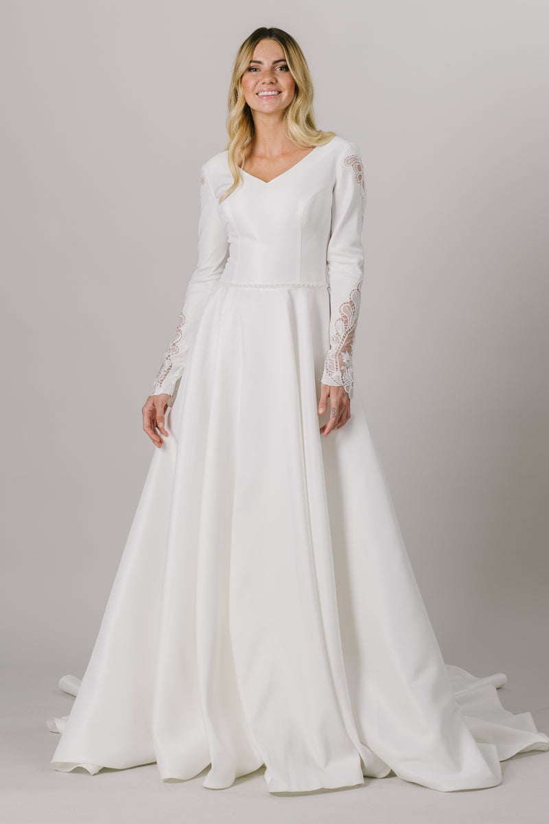 This modest wedding dress features a ballgown silhouette with a stunning v-neck. The long sleeves have a gorgeous sequin lace down the sides. And don't forget about the flattering beaded belt!  Style Love: This dress is part of our brand new, exclusive LatterDayBride wedding dress collection.