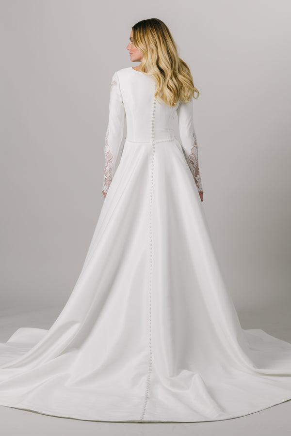 This modest wedding dress features a ballgown silhouette with a stunning v-neck. The long sleeves have a gorgeous sequin lace down the sides. And don't forget about the flattering beaded belt!  Style Love: This dress is part of our brand new, exclusive LatterDayBride wedding dress collection. From a bridal shop called LatterDayBride in downtown Salt Lake City.