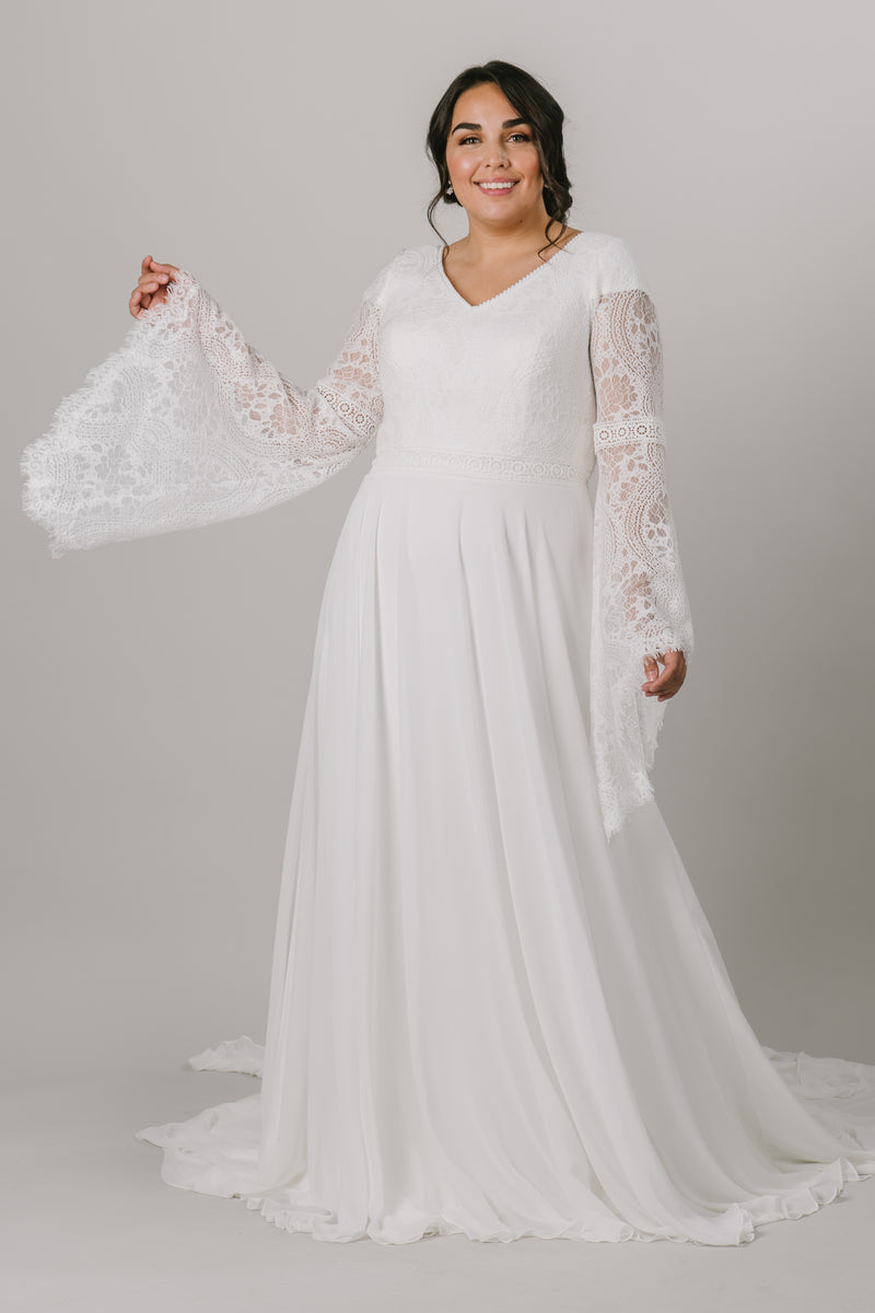 This plus-size modest wedding dress is perfect for our bohemian brides. The A-line silhouette makes it flattering on all figures. The unique lace on the bodice also makes for beautiful, flowy bell sleeves.