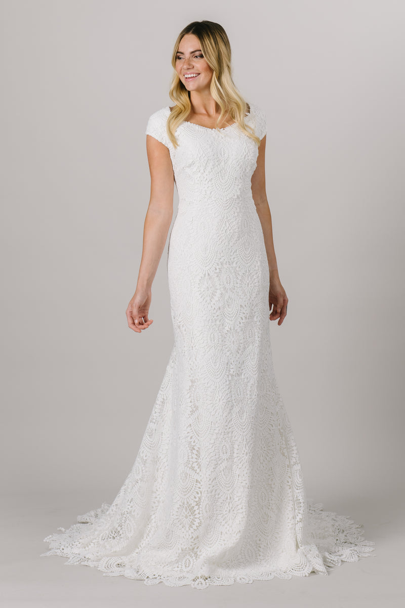 This fitted modest wedding dress features a full, thick lace pattern with dainty little sleeves and a gorgeous neckline somewhere between a sweetheart and v-neckline.   Style Love: This dress is part of our brand new, exclusive LatterDayBride wedding dress collection.