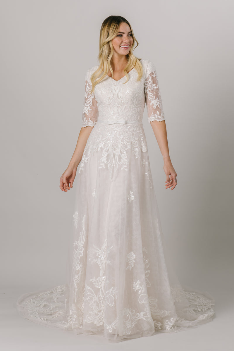 This modest wedding dress has a flattering a-line fit with an absolutely gorgeous lace pattern. With half sleeves and buttons down the back, how could we say no?  Style Love: Little belt with an adorable bow to accentuate the waist!